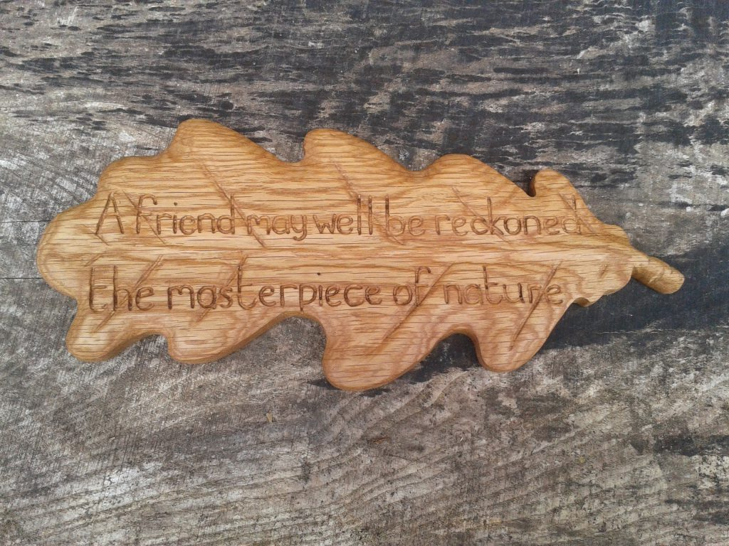 Carving of oak leaf in wood to say thanks
